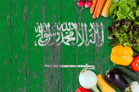 Fresh vegetables from Saudi Arabia on table. Cooking concept on wooden flag background.
