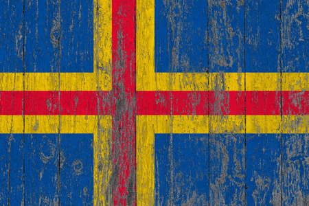 Flag of Aland Islands painted on worn out wooden texture background.