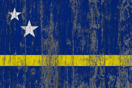 Flag of Curacao painted on worn out wooden texture background.