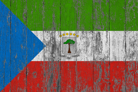 Flag of Equatorial Guinea painted on worn out wooden texture background. Фото со стока