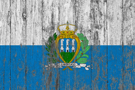 Flag of San Marino painted on worn out wooden texture background.