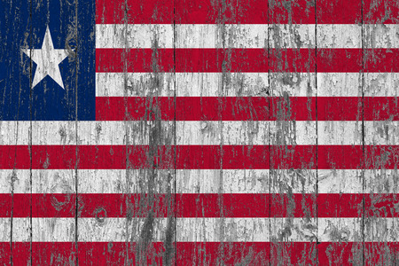 Flag of Liberia painted on worn out wooden texture background.