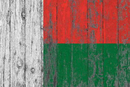 Flag of Madagascar painted on worn out wooden texture background. Stock Photo