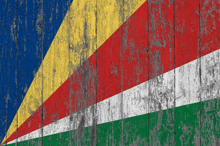 Flag of Seychelles painted on worn out wooden texture background.