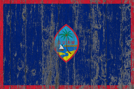 Flag of Guam painted on worn out wooden texture background.