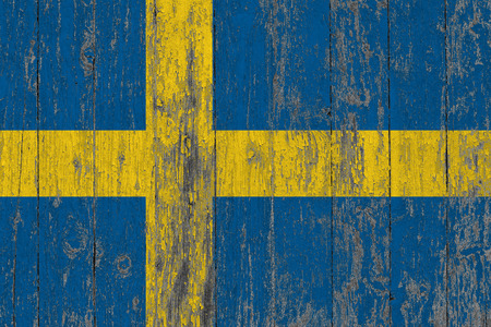 Flag of Sweden painted on worn out wooden texture background. Stock Photo