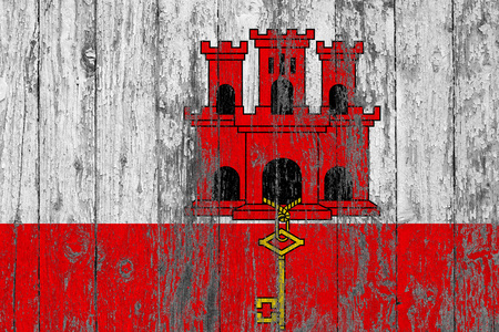 Flag of Gibraltar painted on worn out wooden texture background. Stock Photo