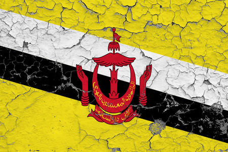 Flag of Brunei painted on cracked dirty wall. National pattern on vintage style surface.