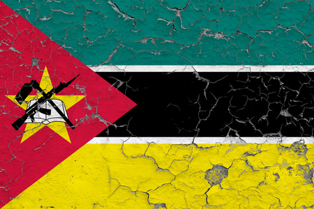 Flag of Mozambique painted on cracked dirty wall. National pattern on vintage style surface.