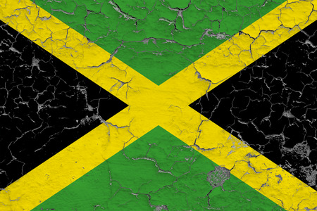 Flag of Jamaica painted on cracked dirty wall. National pattern on vintage style surface.