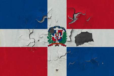 Close up grungy, damaged and weathered Dominican Republic flag on wall peeling off paint to see inside surface.