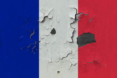 Close up grungy, damaged and weathered France flag on wall peeling off paint to see inside surface.