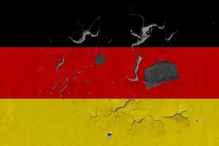 Close up grungy, damaged and weathered Germany flag on wall peeling off paint to see inside surface.