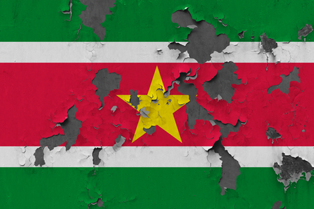 Close up grungy, damaged and weathered Suriname flag on wall peeling off paint to see inside surface. Stockfoto