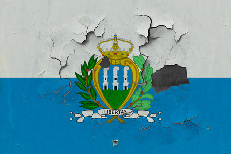 Close up grungy, damaged and weathered San Marino flag on wall peeling off paint to see inside surface. Stockfoto