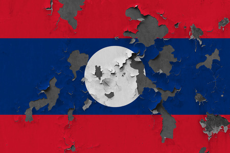 Close up grungy, damaged and weathered Laos flag on wall peeling off paint to see inside surface.