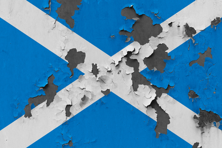 Close up grungy, damaged and weathered Scotland flag on wall peeling off paint to see inside surface. Banque d'images