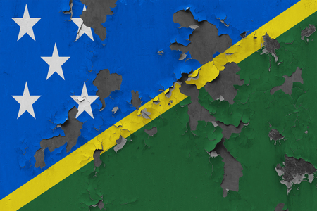 Close up grungy, damaged and weathered Solomon Islands flag on wall peeling off paint to see inside surface. Stok Fotoğraf