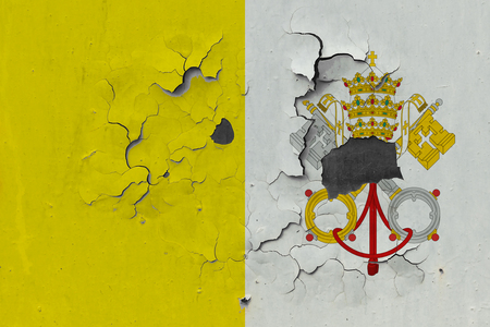 Close up grungy, damaged and weathered Vatican City flag on wall peeling off paint to see inside surface.