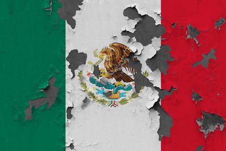 Gros plan sur le drapeau mexicain grungy, endommagé et altéré sur le mur qui se décolle de la peinture pour voir l'intérieur de la surface.