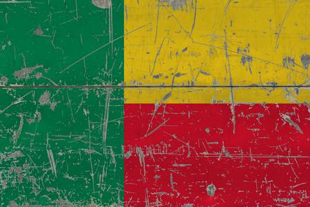 Grunge Benin flag on old scratched wooden surface. National vintage background.