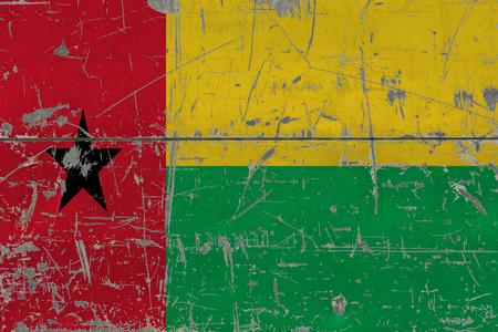 Grunge Guinea Bissau flag on old scratched wooden surface. National vintage background.
