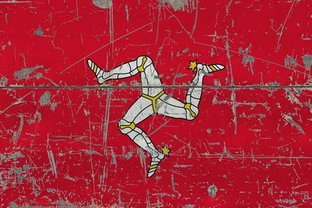 Grunge Isle Of Man flag on old scratched wooden surface. National vintage background.