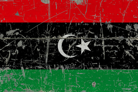 Grunge Libya flag on old scratched wooden surface. National vintage background. 版權商用圖片