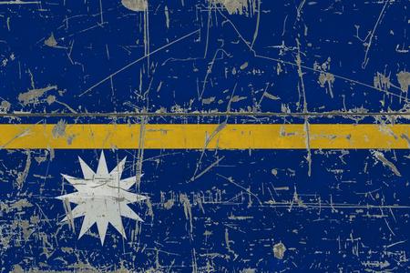 Grunge Nauru flag on old scratched wooden surface. National vintage background.