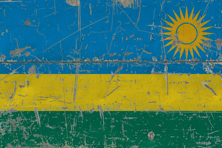 Grunge Rwanda flag on old scratched wooden surface. National vintage background.