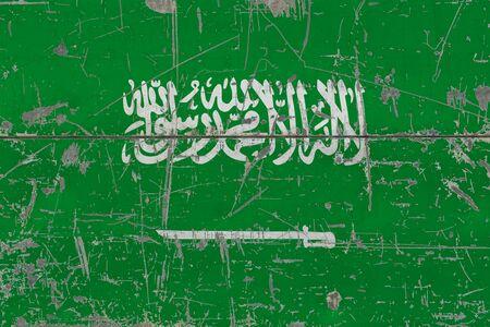 Grunge Saudi Arabia flag on old scratched wooden surface. National vintage background.
