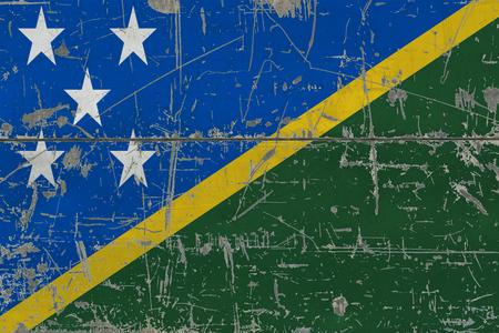 Grunge Solomon Islands flag on old scratched wooden surface. National vintage background.