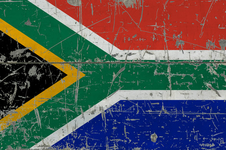Grunge South Africa flag on old scratched wooden surface. National vintage background.