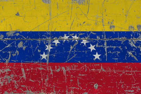 Grunge Venezuela flag on old scratched wooden surface. National vintage background.