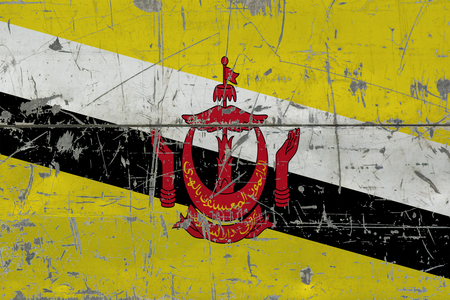 Grunge Brunei flag on old scratched wooden surface. National vintage background.