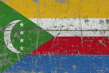 Grunge Comoros flag on old scratched wooden surface. National vintage background.