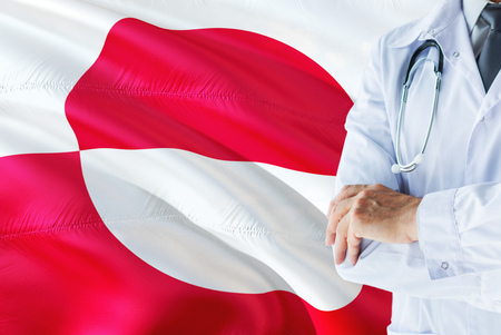 Doctor standing with stethoscope on Greenland flag background. National healthcare system concept, medical theme.