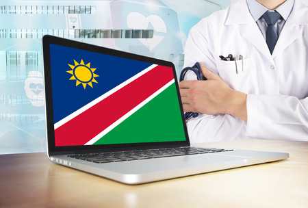 Namibia healthcare system in tech theme. Namibian flag on computer screen. Doctor standing with stethoscope in hospital. Cryptocurrency and Blockchain concept. 스톡 콘텐츠