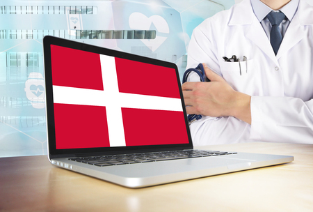 Denmark healthcare system in tech theme. Danish flag on computer screen. Doctor standing with stethoscope in hospital. Cryptocurrency and Blockchain concept.