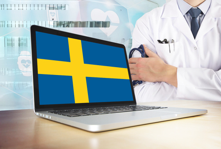 Sweden healthcare system in tech theme. Swedish flag on computer screen. Doctor standing with stethoscope in hospital. Cryptocurrency and Blockchain concept.