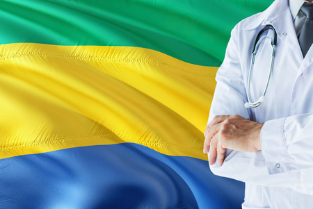 Gabonese Doctor standing with stethoscope on Gabon flag background. National healthcare system concept, medical theme.