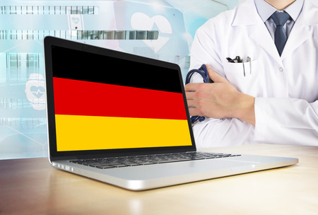 Germany healthcare system in tech theme. German flag on computer screen. Doctor standing with stethoscope in hospital. Cryptocurrency and Blockchain concept. Reklamní fotografie