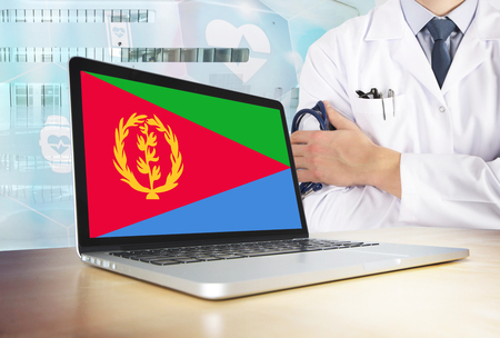 Eritrea healthcare system in tech theme. Eritrean flag on computer screen. Doctor standing with stethoscope in hospital. Cryptocurrency and Blockchain concept. Banco de Imagens