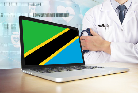 Tanzania healthcare system in tech theme. Tanzanian flag on computer screen. Doctor standing with stethoscope in hospital. Cryptocurrency and Blockchain concept. Banco de Imagens