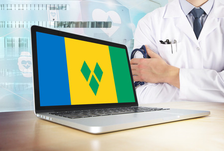 Saint Vincent And The Grenadines healthcare system in tech theme. Flag on computer screen. Doctor standing with stethoscope in hospital. Cryptocurrency and Blockchain concept.