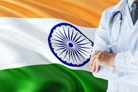 Indian Doctor standing with stethoscope on India flag background. National healthcare system concept, medical theme. Banco de Imagens