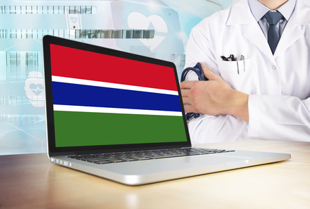 Gambia healthcare system in tech theme. Gambian flag on computer screen. Doctor standing with stethoscope in hospital. Cryptocurrency and Blockchain concept. Banco de Imagens
