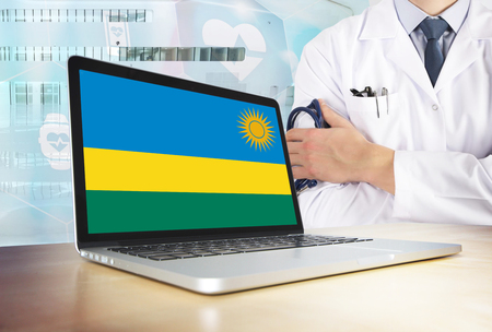 Rwanda healthcare system in tech theme. Rwandan flag on computer screen. Doctor standing with stethoscope in hospital. Cryptocurrency and Blockchain concept.