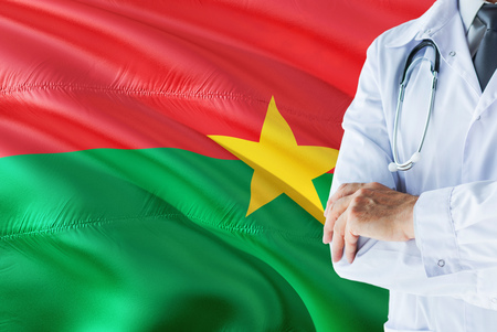Burkinabe Doctor standing with stethoscope on Burkina Faso flag background. National healthcare system concept, medical theme.