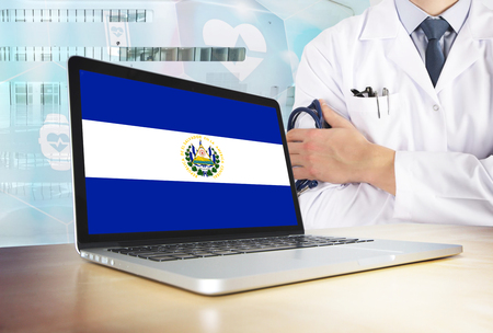 El Salvador healthcare system in tech theme. Salvadoran flag on computer screen. Doctor standing with stethoscope in hospital. Cryptocurrency and Blockchain concept.